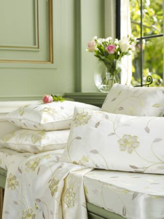 Prestigious Textiles -  Indulgence Fabric Collection - White cushions with oyster white flower stitching on a white bench seating pad with a floral pattern for a classic house setting