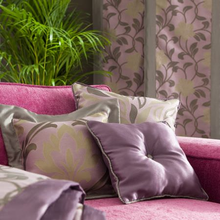 Prestigious Textiles -  Inspirations Fabric Collection - Faded purple cushions with a classic design on a modern upholstered couch, and a purple curtain with floral and foliage pattern