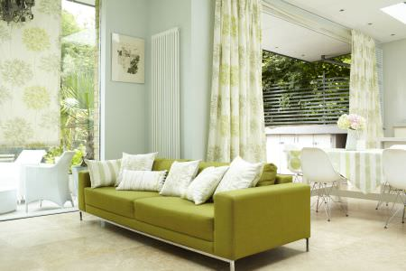 Prestigious Textiles -  Intuition Fabric Collection - White cushions with green stripes on a modern green upholstered couch, and white curtains with green flower impressions