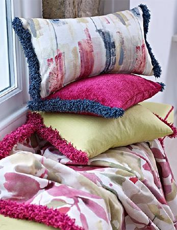Prestigious Textiles -  Iona Fabric Collection - Thick, fluffy, tasseled fringing on rectangular cushions and a floral throw, all in bright pink, citrus, white and navy blue