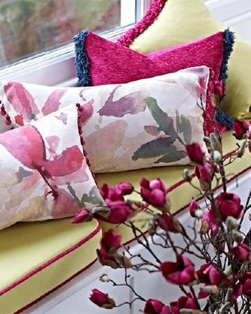 Prestigious Textiles -  Iona Fabric Collection - Citrus seat cushions on a window seat, and fluffy trims on pink, white and green plain, floral and textured scatter cushions