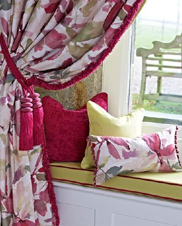 Prestigious Textiles -  Iona Fabric Collection - A tassel tieback, floral curtains, plain and patterned scatter cushions and a window seat, all in white, citrus and bright red