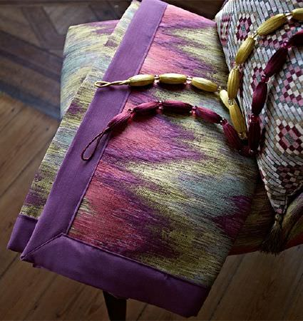 Prestigious Textiles -  Iona Fabric Collection - A pink, green and purple patterned throw folded on a mosaic style diamond print padded armchair with 2 strings of beads