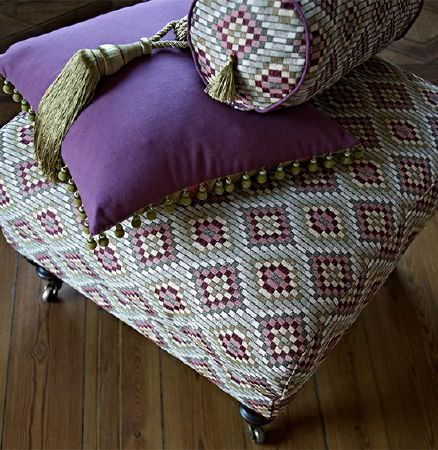 Prestigious Textiles -  Iona Fabric Collection - White, blue, pink, grey, and red mosaic style diamond print bolster cushion and footstool, a purple cushion and a green tassel