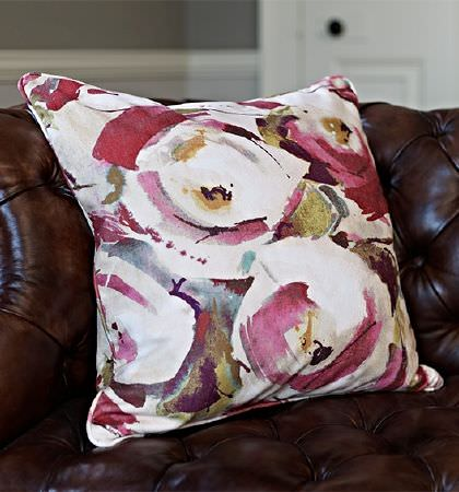 Prestigious Textiles -  Iona Fabric Collection - A large, bold, stylised floral print cushion made in red, white and khaki shades, placed on a dark brown leather sofa