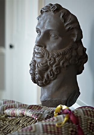 Prestigious Textiles -  Iona Fabric Collection - A dark brown bearded bust sculpture with swathes of mosaic style diamond print patterned fabric with a khaki trim