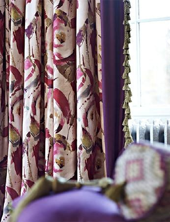 Prestigious Textiles -  Iona Fabric Collection - Curtains made with a large, stylised red, white and green floral print, edged in purple fabric, with a green tassel trim