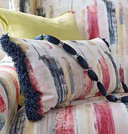 Prestigious Textiles -  Iona Fabric Collection - Navy beads on a red, white, blue-grey and beige printed cushion with fringing, a matching armchair and a yellow cushion