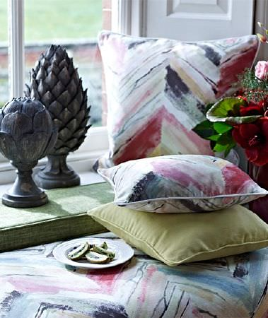 Prestigious Textiles -  Iona Fabric Collection - A large herringbone design printed roughly in grey and pink, on window seat and scatter cushions, with a plain cushion