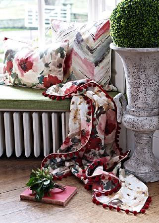 Prestigious Textiles -  Iona Fabric Collection - A bold floral printed throw and cushion with a larger patterned cushion on a green padded window seat beside a large urn