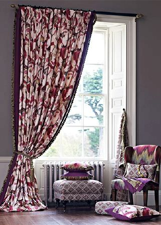 Prestigious Textiles -  Iona Fabric Collection - Long floral curtains with a patterned armchair, footstool and cushions, all in bright shades of purple, pink, green and red