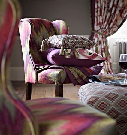 Prestigious Textiles -  Iona Fabric Collection - Bright shades of purple, pink, green and grey making up patterned armchairs, cushions with tassels, curtains and a footstool