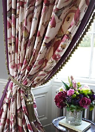 Prestigious Textiles -  Iona Fabric Collection - Large red-pink and cream coloured floral curtains with a stylised design and a tassel fringe and a khaki tassel tieback