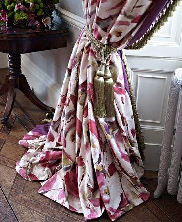 Prestigious Textiles -  Iona Fabric Collection - A metallic khaki green tassel tieback around bold, stylised floral patterned pink, purple and cream floor-length curtains