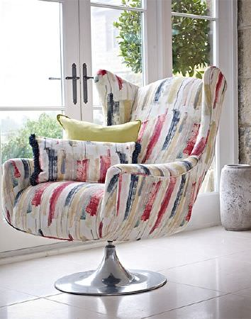 Prestigious Textiles -  Iona Fabric Collection - A swivel armchair on a silver base, with a roughly printed design in red, white, blue-grey and beige, with two cushions