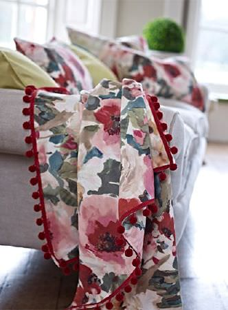 Prestigious Textiles -  Iona Fabric Collection - Large multicoloured florals on a throw with a red pompom trim, on a grey armchair with floral and plain yellow cushions