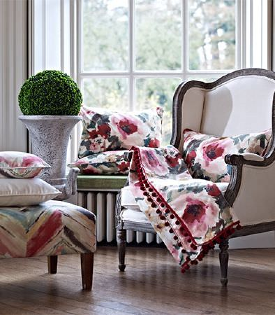 Prestigious Textiles -  Iona Fabric Collection - A floral print throw and cushion on a white armchair with a wooden frame, with a patterned footstool and two cushions