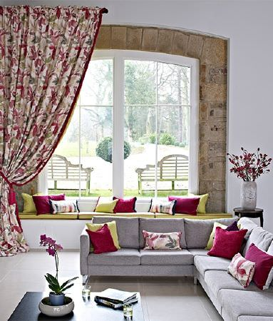 Prestigious Textiles -  Iona Fabric Collection - Bold floral floor-length curtains, with plain bright red and citrus cushions on a grey corner sofa and green window seat