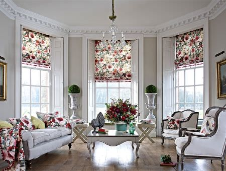 Prestigious Textiles -  Iona Fabric Collection - A white sofa and wood framed armchairs with floral print blinds, cushions and a throw, with stools and a white coffee table
