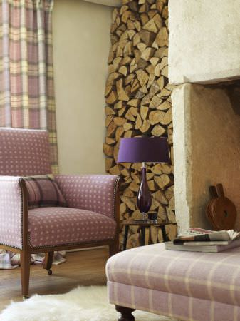 Prestigious Textiles -  Isles Of Skye Fabric Collection - A country type armchair with purple upholstery with white dots, a purple and white tartan curtain and a plaid purple footstool