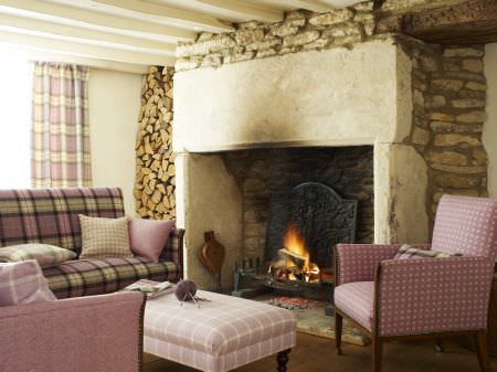 Prestigious Textiles -  Isles Of Skye Fabric Collection - A country house living room with a couch with purple plaid upholstery, and upholstered armchairs and footstool