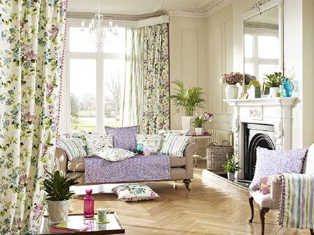 Prestigious Textiles -  Italian Gardens Fabric Collection - Beige sofa, pastel coloured striped and floral fabric curtains, blankets and cushions, with square table, white vases, mirror, wicker basket