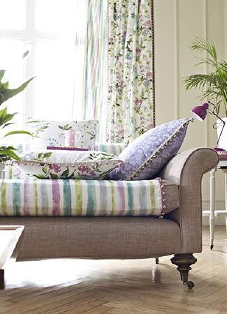 Prestigious Textiles -  Italian Gardens Fabric Collection - Light brown sofa, with striped fabric, purple patterned cushion, floral cushion and floral curtains, all with beaded edges, and a pink lamp