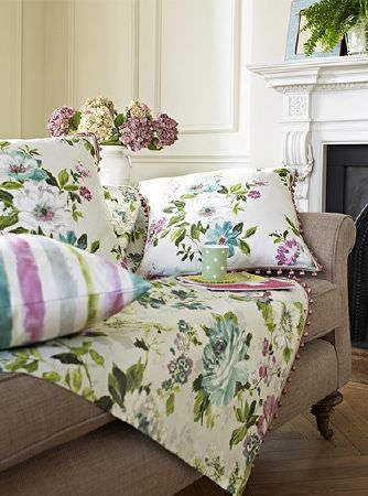 Prestigious Textiles -  Italian Gardens Fabric Collection - Pastel coloured floral throw and cushions with pink bead fringing, with a striped cushion, on a brown fabric sofa, with a white vase