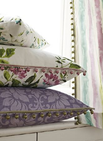 Prestigious Textiles -  Italian Gardens Fabric Collection - Purple patterned cushion with gold bead fringing, floral cushion with pink bead fringing, floral cushion, striped curtain with bead fringe