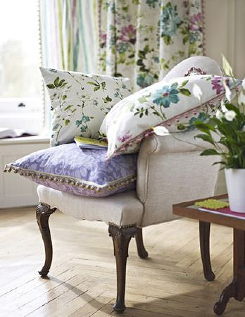 Prestigious Textiles -  Italian Gardens Fabric Collection - Beige armchair with three floral and patterned cushions, beside a square side table with a white vase, and floral and striped curtains
