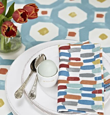 Prestigious Textiles -  Java Fabric Collection - Dusky shades of blue, red, brown, gold and white on a streaked and geoemetric patterned napkin and tablecloth, with crockery