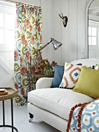 Prestigious Textiles -  Java Fabric Collection - Curtains, cushions and a throw made with plain and patterned white, light blue, dusky red and green fabrics, on a white sofa