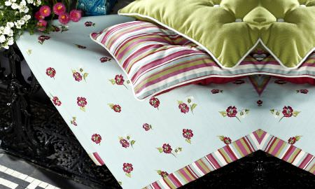 Prestigious Textiles -  Jubilee Fabric Collection - Traditional rose design fabric with striped edge, and showing matching cushions in blue, green, red and white.