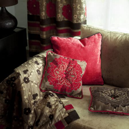 Prestigious Textiles -  Kansai Fabric Collection - Red and brown cushions with floral images on a light brown upholstered couch with a silver brown quilt
