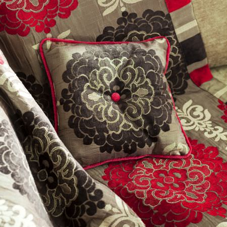 Prestigious Textiles -  Kansai Fabric Collection - A silver cushion with red edges and a black classic floral design on a grey quilt with a classic red and white floral pattern