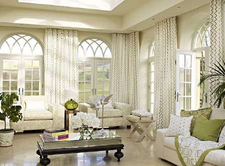 Prestigious Textiles -  Kasra Fabric Collection - Plain and patterned cream sofa and armchairs, long zigzag print curtains, green and white cushions and blanket, wood and glass coffee table