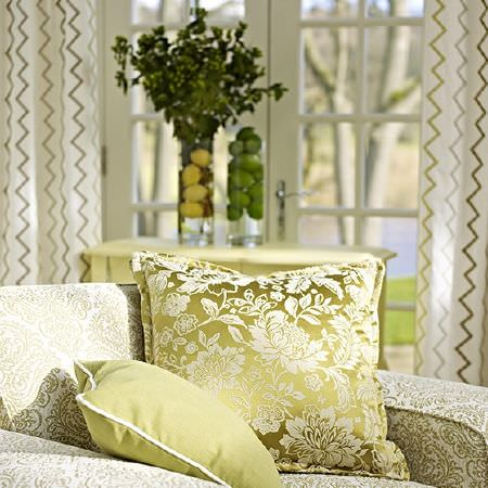 Prestigious Textiles -  Kasra Fabric Collection - Luxurious green cushions, one with a white pattern, on a white and green patterned armchair, with zigzag print curtains, a table and glass vases