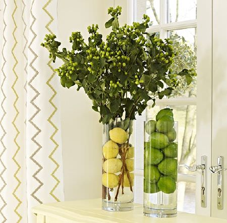 Prestigious Textiles -  Kasra Fabric Collection - Two cylindrical glass vases filled with fruit and flowers, on a cream coloured side board, with cream, green and grey zigzag print curtains