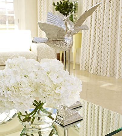 Prestigious Textiles -  Kasra Fabric Collection - Mirror-topped table with two silver bird sculptures, a round clear glass vase, a cream patterned sofa and curtains with a zigzag pattern