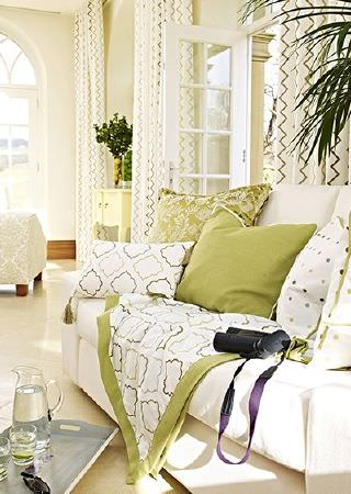 Prestigious Textiles -  Kasra Fabric Collection - Patterned and plain scatter cushions and a throw in shades of green and cream, on a cream sofa, with zigzag print curtains, a tray and jugs