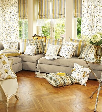 Prestigious Textiles -  Lago Fabric Collection - Beige corner sofa with green-gold and grey-blue striped blinds, floral curtains, and striped, floral and patterned cushions, and silver table