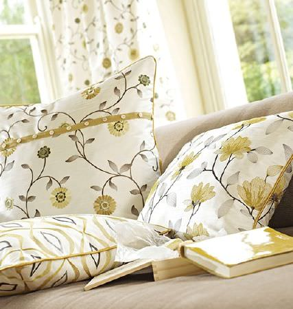 Prestigious Textiles -  Lago Fabric Collection - Cushions with a cream background and green-gold and grey floral and geometric patterns, with matching curtains and a beige sofa
