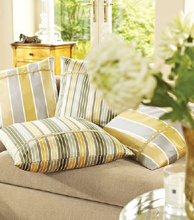 Prestigious Textiles -  Lago Fabric Collection - Gold, grey, black, green and cream striped cushions with button detail, on a beige sofa, with a silver table and a wooden chest of drawers