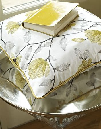 Prestigious Textiles -  Lago Fabric Collection - Cream cushion embroidered with green flowers and light grey leaves, on a table made from a silver tray and silver branches for legs