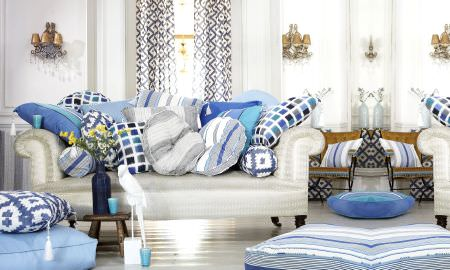 Prestigious Textiles -  Lakota Fabric Collection - Cream sofas with a selection of striped, checked and mosaic patterned cushions in blues, greys and white, and matching curtains