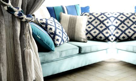 Prestigious Textiles -  Lakota Fabric Collection - Soft light brown curtain with curtain tie, opening to living space with light teal sofa and striped and checked sofa cushions