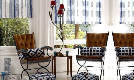 Prestigious Textiles -  Lakota Fabric Collection - Checked floor cushions, striped Roman blinds allowing light into relaxed seating area
