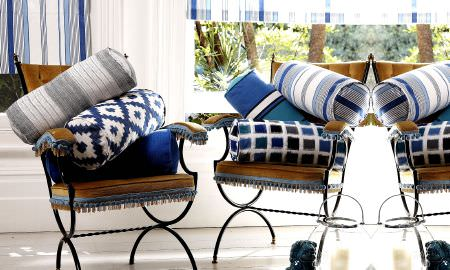 Prestigious Textiles -  Lakota Fabric Collection - Metal chairs with tasselled cushions, and a selection of cylindrical striped and checked cushions