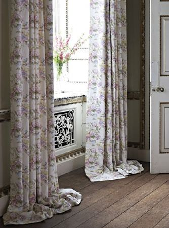 Prestigious Textiles -  Langdale Fabric Collection - Pink flowers placed in a clear glass bell jar vase on a wooden window seat with elegant grey and white floral curtains