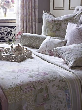 Prestigious Textiles -  Langdale Fabric Collection - A bed with a duvet, throw and various scatter cushions, all made with florals, stripes and patterns in pale shades of grey